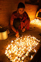 woman lighting candle lights in the night during dashein festival time in Newar city Bhaktapur, Kathmandu valley, Nepal, October 2011. God of fire (Agni) goes back to vedic times, when Shiva and Brahma were still unknown. Fire (like other elements - water, light, earth, colorful minerals, flowers,  etc) are very important in Hindu rituals since thousands of years.