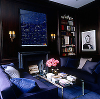 A contemporary drawing of Abraham Lincoln sets the tone in this dark living room with wooden panelling and a blue colour palette