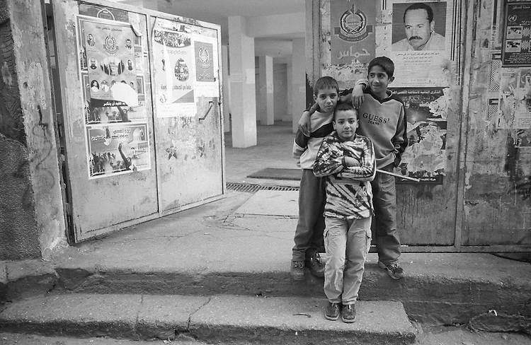 Shatila, UNRWA camp. Khaled, Tarek and Hussain (front) ar at the door of the only UNRWA school inside the camp. Due to limited space, schools shift classes: The &quot;Ramallah&quot; school for boys becomes the &quot;Hama&quot; school for girls in the afternoon. The sequence is changed every month.<br />  <br /> Chatila, camp de l'UNRWA. Khaled, Tarek et Hussein (premier plan) sont devant la seule &eacute;cole de l'UNRWA &agrave; l'int&eacute;rieur du camp. A cause de l'espace limit&eacute;, l'&eacute;cole &laquo;Ramallah&raquo; pour gar&ccedil;ons devient l'&eacute;cole &laquo;Hama&raquo; pour filles l'apr&egrave;s-midi. Chaque mois l'ordre est chang&eacute;...