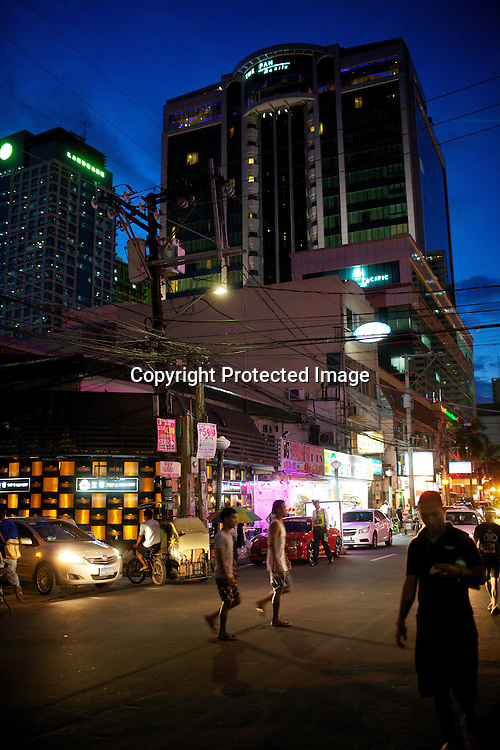 Pedestrians walk past a busy intersection at dusk in Malate, Manila in the Philippines. Photo: Sanjit Das