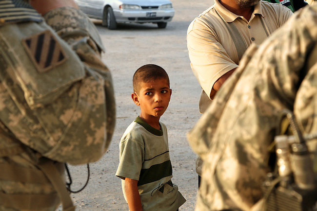 A boy watches a U.S. soldier as a group of local men are questioned by U.S. forces about Shiite militia activities in an area called the Four Corners, southeast of Baghdad, Iraq. Sept. 13, 2007. DREW BROWN/STARS AND STRIPES