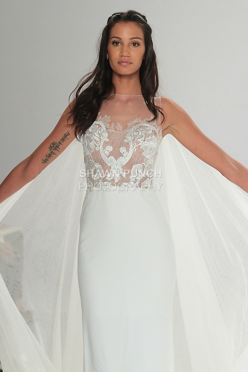 "Model walks runway in Taranis - an off white Georgette sheath dress with a lace bodice and a tulle train embellished with a Guipure hemline, from the Tony Ward Fall 2016 ""A Mid-Summer Night's Dream"" bridal collection on April 18, 2016 at Kleinfeld Bridal during New York Bridal Fashion Week Spring Summer 2016."