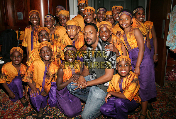 DAMIEN HORNE with the African Children's Choir.Nashville 4 Africa Concert held at the Schermerhorn Symphony Center, Nashville, TN, USA..April 22nd, 2009.full length jeans denim grey gray waistcoat kneeling crouching yellow purple traditional outfits dress kids.CAP/ADM/RR.©Randi Radcliff/AdMedia/Capital Pictures.