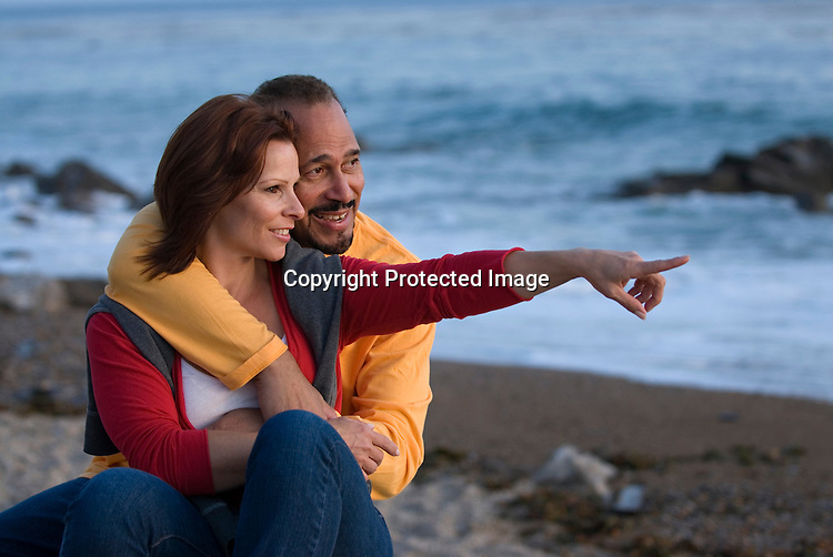 Happy couple at beach, she pointing at interesting view