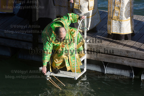 Greek catholic priest puts candles into the water as he sanctifies the water of river Danube on the occasion of Epiphany in central Budapest, Hungary on January 06, 2017. ATTILA VOLGYI