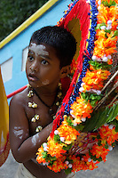 boy carrying offerings while ascending stairways to sanctuary  of Batu Caves, Thaipusam ceremonies,  Kuala Lumpur, Malaysia, 2012. Thaipusam ceremonies, celebrated by tamile Hindu community in Malaysia, take place  in Sanctuary of Batu Caves at the border of Kuala Lumpur, each year around end of January or beginning of February, according to Hindu moon calendar. The event is paying hommage to Lord Murugan, a spirit or god created by Shiva to lead the army of gods against the army of evil demons, finally defeating the evil spirits. There are many ways to present offerings or sacrifices for this major religious event. Devotees mortify their bodies by carrying heavy kavaris with spears fixed in their skin or fruits, flowers and little post with holy milk fixed with hooks in their skin, ascending the stairways to the sanctuary in trance, `followed by assistant  taking care and musicians playing loud and fast rhythmic trance music.  Many families shave their head in a ritual before ascending the stairways, as part of rituals to obtain salvation for their ancestors.