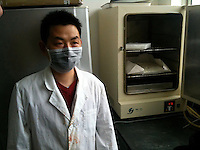 A worker is seen next to a machine containing an unidentified 'new product' similar to MDPV at a laboratory belonging to CEC Limited, a company which exports the legal high to Great Britain, Pudong, Shanghai, China, 08 April 2010.
