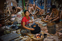 Myanmar/Burma, Yangon, N. Okkalapa region. Daw Nyunt Nyunt Yee runs a guitar building shop and she got a BRAC loan for supplies. The air is thick and smells of chemicals as the heavy varnish, paint and glue needs to be heated over a hot fire, with no ventilation in the room crowded with workers. 15-16 people work here and they can make about 200 guitars a week, the dealer pays about $15 per piece. She makes about $400 per week take home pay. She has one 8 year old child, a student.