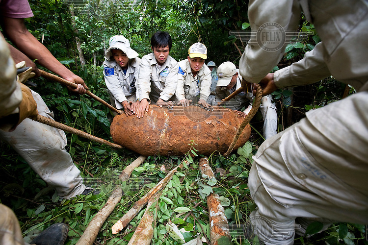 A team from Handicap International carefully retrieve this bomb that weighed 1000 pounds in order to dismantle it. Decades on, Laos is still living with the effects of the Vietnam war. Millions of bombs were dropped by US aircraft in Laos in an attempt to destroy the supply lines of North Vietnamese forces. Many remain deadly, with frequent accidents involving unexploded ordnance (UXO)..
