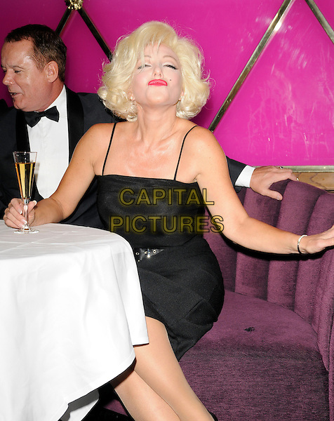 "LOUIS HOOVER & SUNNY THOMPSON .At the ""When Marilyn Met...Frank Sinatra, Dean Martin & Sammy Davis Jr."" photocall, Le Pigalle Club, Piccadilly, London, England, UK, .2nd September 2009..half length sitting at table re-creation scene lookalike lookalikes look-a-like glass of champagne drink black tux bow tie tuxedo dress puckering .CAP/CAN.©Can Nguyen/Capital Pictures"