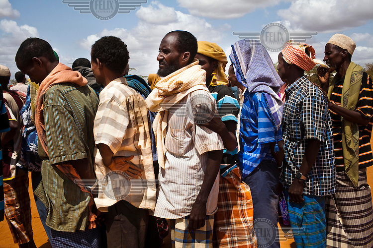 Somali refugees wait in a line outside the registration and food distribution point at the IFO camp, part of the Dadaab refugee camp in Kenya. The drought is the worst in East Africa for 60 years. The UN described it as a humanitarian emergency. The already overcrowded complex received 1,000 new refugees a day in June, five times more than a year ago. About 30,000 people arrived at the Dadaab refugee camp in June, according to UNHCR compared to 6,000 in June 2010.
