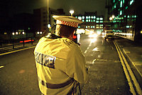 Traffic police officer performing speed enforcement checks using a handheld laser equipped speed measuring device at night. The officer points the unit at an on-coming vehicle and the speed is shown on the back of the gun. This image may only be used to portray the subject in a positive manner..©shoutpictures.com..john@shoutpictures.com
