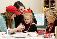 NWA Democrat-Gazette/DAVID GOTTSCHALK  Eden Hobson, 5, decorates a goodie bag, Tuesday, February, 14, 2017, with Ferrin Webb (from left), a senior and Pre-School Teacher at the University of Arkansas Autism Research Clinic, her mother Alison and Kaitlin McMurrian (cq), a graduate student, during a Valentines Day Party on the campus in Fayetteville. The pre-school students and alumni students participated in the activities that included making a Valentines Day Ladybug, decorate goodie bags, making a strawberry shortcake and participating in Valentines Day learning activities.