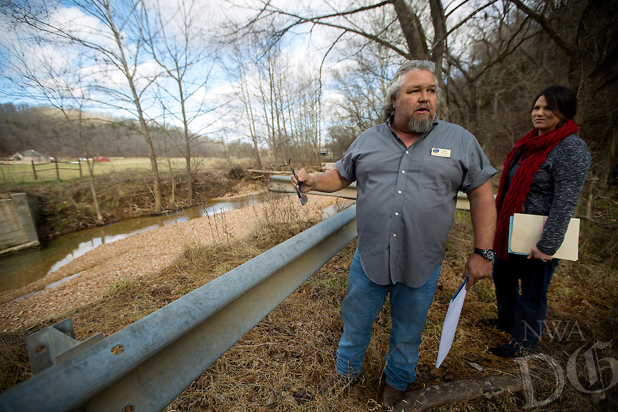 NWA Democrat-Gazette/JASON IVESTER<br /> Jeff Clark and Ashley Kirby, both with Benton County Road Department, look over a site on Friday, Jan. 15, 2016, where a bridge once crossed Limekelm Hollow Creek as part of Corinth Road in Garfield.