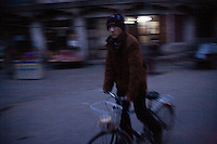 A Uighur boy rides a bike through the streets of the Old Town section of Kashgar, Xinjiang, China.