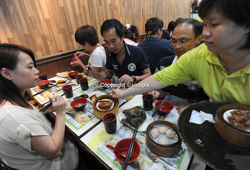 Customers inside the original Tim Ho Wan the cheapest (and probably smallest) Michelin starred restaurant in the world, Hong Kong..17-Jul-11..Photo by Richard Jones......