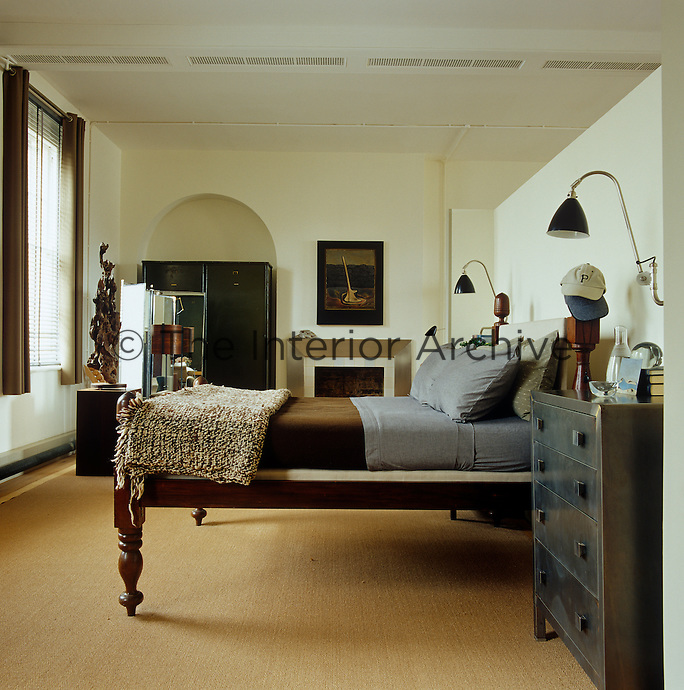 Bedding in tones of grey and brown on the 19th century Burmese bed create a masculine yet tranquil feel in the sleeping area