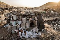 HERAT, AFGHANISTAN - OCTOBER 03, 2013: An Afghan man addicted to opium, sleeps near his stone-built shelter covered with cloth, after having smoked on the outskirts of the city, in a drug community comprising of at least 500 addicts, on October 03, 2013 in Herat, Afghanistan.