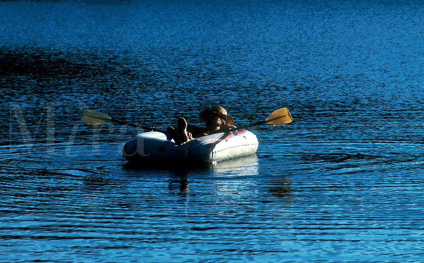 SENIOR MAN FLOATING IN A RAFT ON A LAKE. Cape Cod, MA