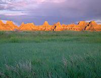 SDBD_007 - USA, South Dakota, Badlands National Park, Sunrise light on eroded pinnacles above spring green prairie grasses, near Castle Trail, North Unit.