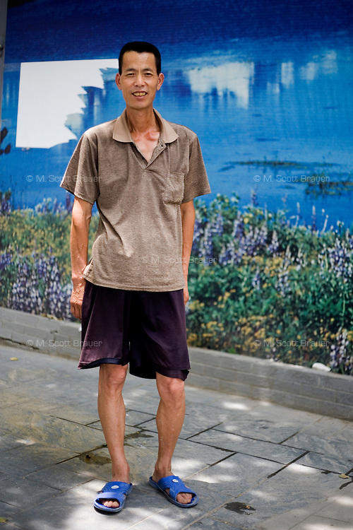 Wangfeile, a guard at a construction site, age 48, poses for a portrait in Nanjing. Response to 'What does China mean to you?': 'A harmonious society. Too focused on wealth.'  Response to 'What is your role in China's future?': 'A strong nation with a cultured and righteous society.'