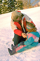 Father helping daughter with snow suit while sledding age 35 and 4.  St Paul  Minnesota USA