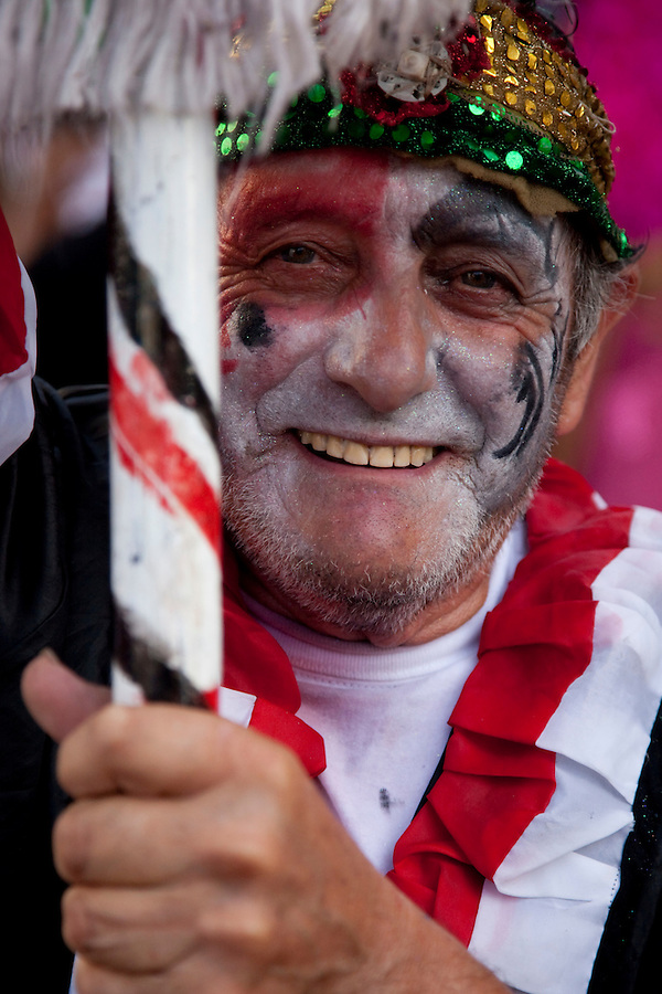 An elderly man bears a flag during the parade of Llamadas in Montevideo's Carnaval.  One of the most imporant elements of Carnaval in Uruguay is Candombe, an African drum rhythm played on tambor drums.  It was revitalized in the Americas by black slave descendents as a way by which to reclaim their cultural heritage and battle for civil rights.