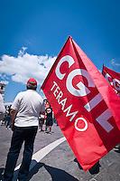 Un operaio con la bandiera della CGIL durante lo Sciopero Nazionale della CGIL, in Abruzzo il corteo della protesta si è svolta nella zona rossa della città de L'Aquila ad un anno dal terremoto. 25/06/2010 Photo: Adamo Di Loreto/BuenaVista*Photo