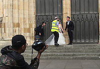 A Chinese couple are moved on by security at York Cathedral, UK.  An increasing number of Chinese couple are having their wedding photos taken in the English country-side, classic towns and monuments to show in China. <br /> <br /> Photo by Richard Jones/ Sinopix