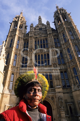 London, England. Paulinho Payakan (Bep Koroti Kayapo), international figurehead for the Kayapo, outside the Houses of Parliament in Westminster wearing his feather cocaa and black war paint; 1989.