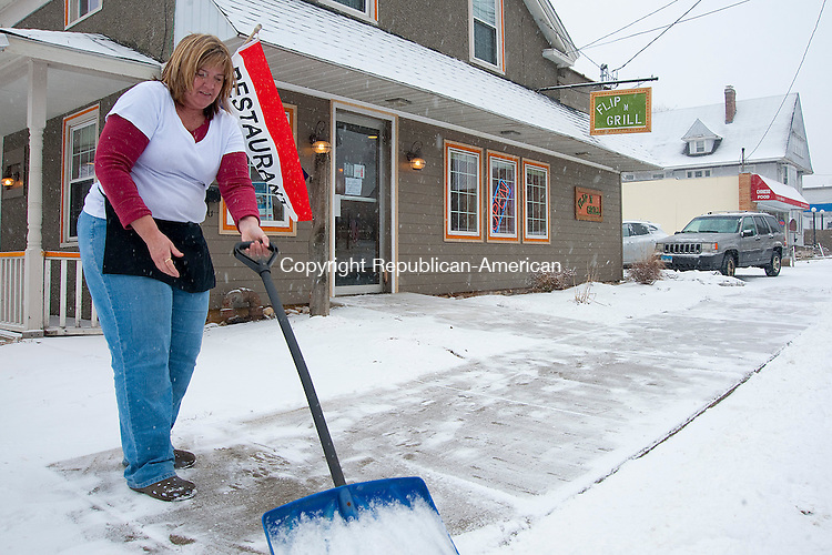 WINSTED, CT 08 FEBRUARY 2013- --020813JS04--Lorie Bates, owner of Flip N Grill in Winsted, clears the snow off the sidewalk outside her restaurant on Friday. .Jim Shannon Republican American .