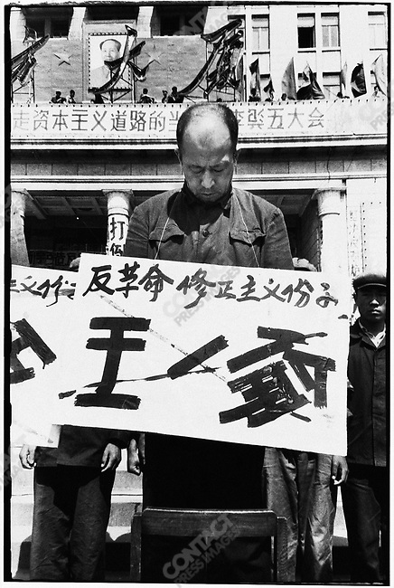 "Forced to stand on chairs in front of the North Plaza Hotel, the seven secretaries of the Heilongjiang Party committee are denounced for ""carrying out Liu Shaoqi's revisionist line."" Each wears a placard with his name crossed out and a description of his alleged crime. Here, Wang Yilun. Harbin, 27 April 1967"