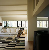 Wall to wall windows allow plenty of light into the living room. A white sofa and an Eames aluminium chair sit on a brown and beige rug.