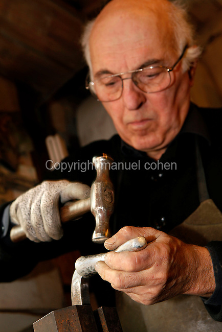Dans son atelier parisien, le 20 janvier 2011, le sculpteur orfèvre Goudji travaille des pièces de futures créations. Portrait de l'artiste au travail. In his Parisian studio, on January 20, 2011, goldsmith Goudji is working new creations of his trade. Portrait of the artist working. Born in Georgia in 1941, Goudji has lived in Paris since 1974, due to the personal intervention of President Georges Pompidou. Here he produces his numerous contemporary works of goldsmithery in such widely differing fields as Church Art, swords, jewellery and sculpture. Picture by Manuel Cohen
