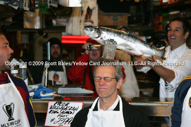 20 November 2009: ESPN broadcaster JP Dellacamera (center) has a water bottle knocked off his head by a flying fish. Major League Soccer players Alan Gordon of the Los Angeles Galaxy and Chris Seitz of Real Salt Lake took part in a fish toss at Pike Place Market in Seattle, WA as part of the Major League Soccer MLS Cup weekend activities.
