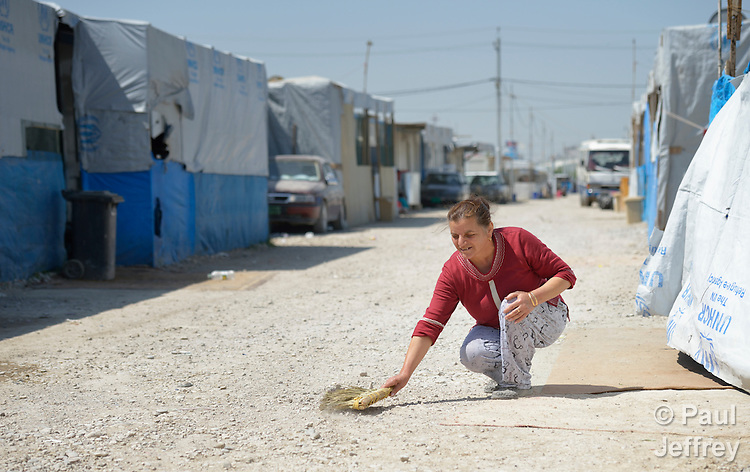 A woman sweeps the street in front of her shelter in a camp for internally displaced families in Ankawa, near Erbil, Iraq, on April 8, 2016. Residents of the camp, mostly Christians, were displaced from Mosul, Qaraqosh and other communities in Iraq when ISIS swept through the area in 2014.