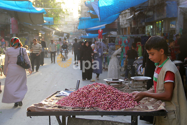 A Syrian boy sells pistachio in a market in a rebel-controlled area in the northern Syrian city of Aleppo, on August 31, 2015. Photo by Ameer al-Halbi