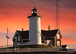 The Historic And Beautiful Nobska Point Lighthouse In Early Morning Light With A Deep Red Sky As Background, Woods Hole, Cape Cod, Massachusetts, USA