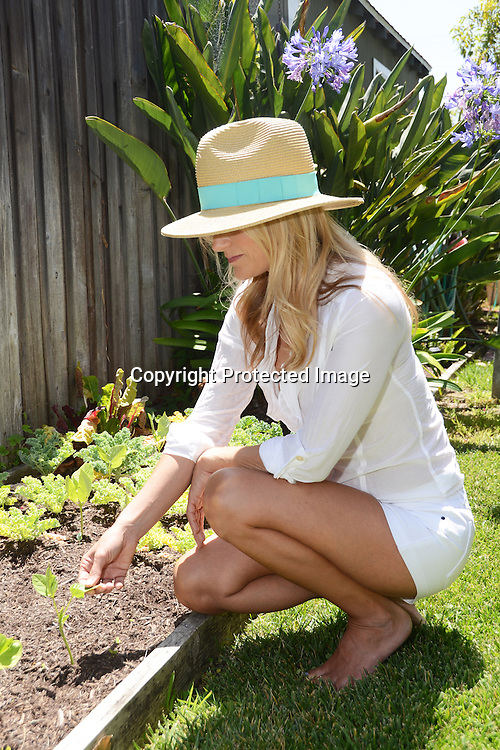 Woman with her sun hat in a garden Stock Photo
