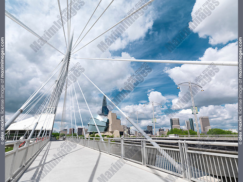 Esplanade Riel Footbridge with the Canadian Museum for Human Rights and downtown skyline under beautiful cloudy sky in the background. Winnipeg, Manitoba, Canada 2017.