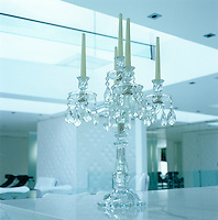 A crystal candelabra stands on the marble-topped work surface in the kitchen