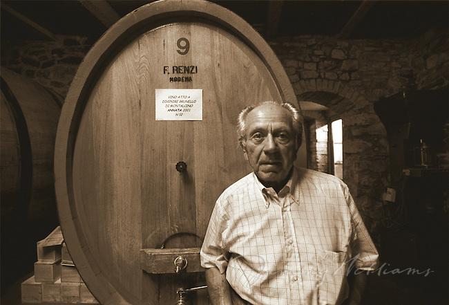 An elderly winemaker stands in the cellar with his wine barrels.
