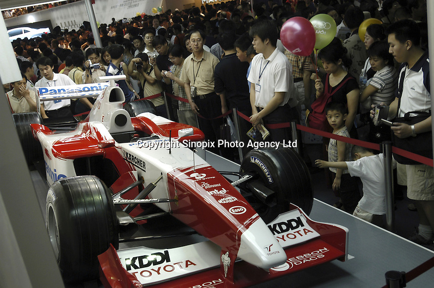 Visitors look at a Formula 1 Racing car at the Auto China 2004 exhibition in Beijing, China..