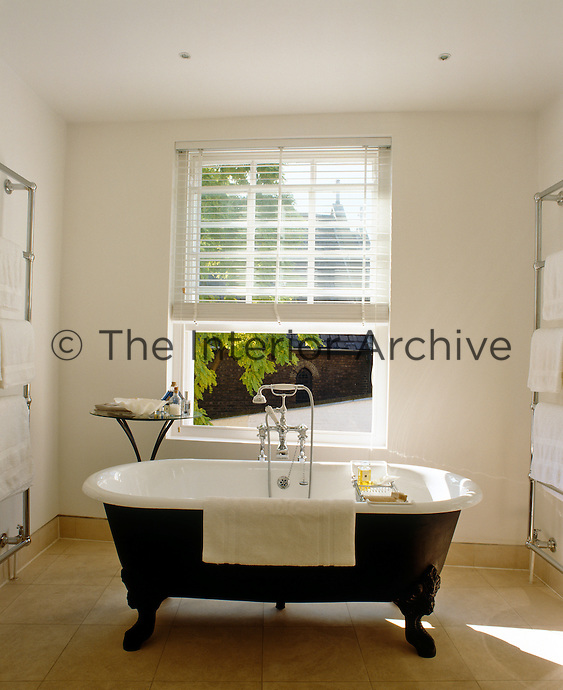 A free-standing bath is flanked by a pair of heated chrome towel rails in a bathroom which has a window opening onto the patio