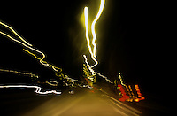 Blurred tail lights of highway traffic at night.
