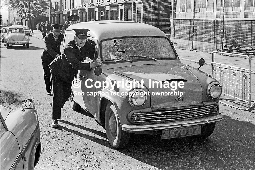 Police push away the van in which Harry Thornton, from Crossmaglen, Co Armagh, died in a shooting incident on the Springfield Road, Belfast, around the time of the introduction of internment. 339/71, 197108070336b.<br />