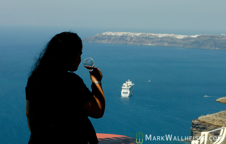 A cruise ship sits in the caldera at the island of Santorini, Greece.
