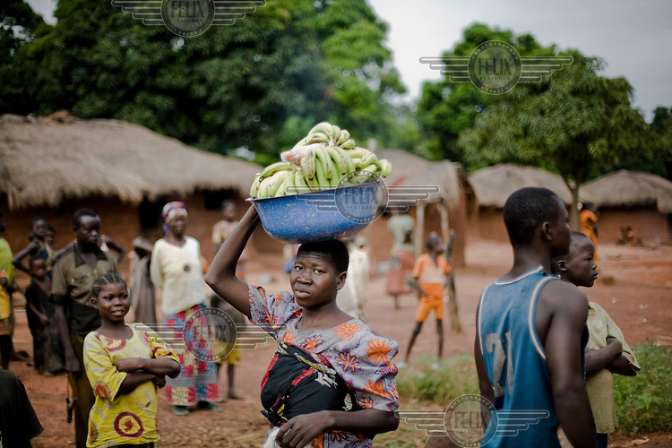 Outside their huts, a group of villagers look on as a woman carries a bowlful of bananas on her head.