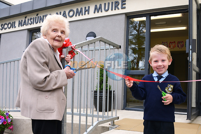 The youngest pupil at Scoil Mhuire National School in Donore, five year old Mark Craven, and 83 year old past pupil Kitty Campbell combine forces to cut the tape at the official opening of the new extension at the school.  Photo: Andy Spearman.