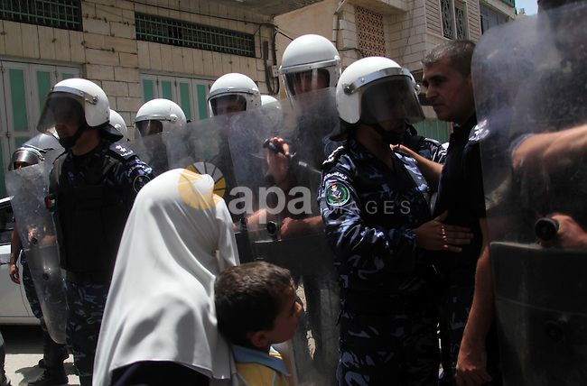 A Palestinian woman gestures in front of riot police during a protest to show solidarity with prisoners on hunger strike in Israeli jails, in the West Bank city of Hebron on June 20, 2014. Israel is to rush through a bill allowing force-feeding of hunger-striking prisoners, a newspaper reported on June 17, 2014 as 80 Palestinian inmates were hospitalised after refusing to eat for nearly two months. Photo by Mamoun Wazwaz